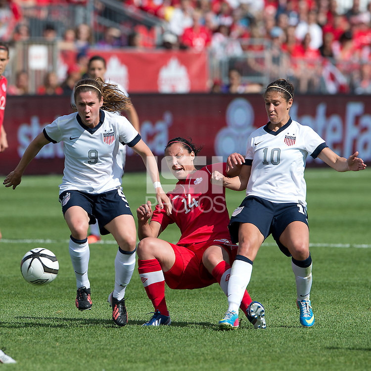 02 June 2013: U.S Women's National Soccer Team midfielder Heather O'Reilly #9 and U.S Women's National Soccer Team midfielder Carli Lloyd #10 battle for a ball with Canadian National Women's Soccer Team player Melissa Tancredi #14 during an International Friendly soccer match between the U.S. Women's National Soccer Team and the Canadian Women's National Soccer Team at BMO Field in Toronto, Ontario.<br /> The U.S. Women's National Team Won 3-0.