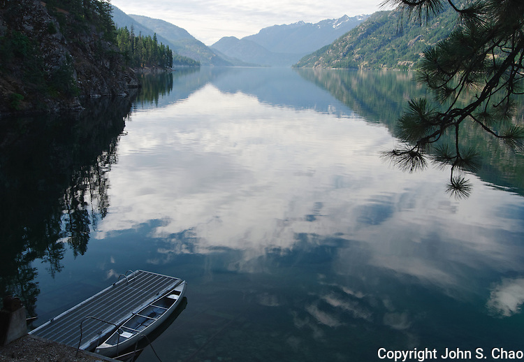 A moored canoe sits on mirror still waters of Lake Chelan at dawn in Stehekin, North Cascades National Park, Washington State