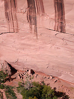 Steep sandstone walls with desert varnish stains tower over the ancient Anasazi ruins in Canyon de Chelly National Monument near Chinle, Arizona USA - October 23, 2006.  Canyon de Chelly, located within the Navajo nation in northeastern Arizona, is still inhabited and farmed by the Navajo community today.