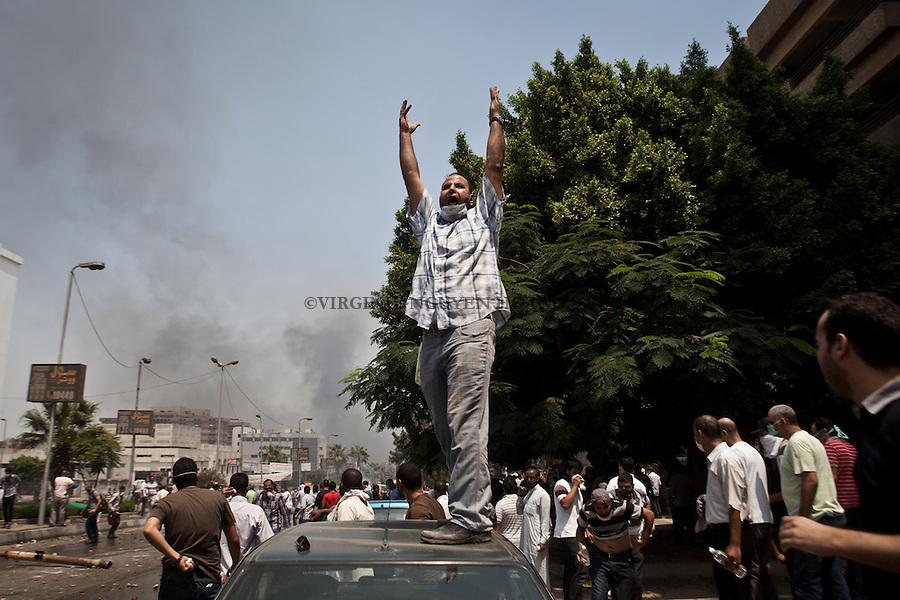 Un homme appelle à manifester devant les policiers qui bloquent l'accès au sit-in de Rabaa, Nasr City, Le Caire.