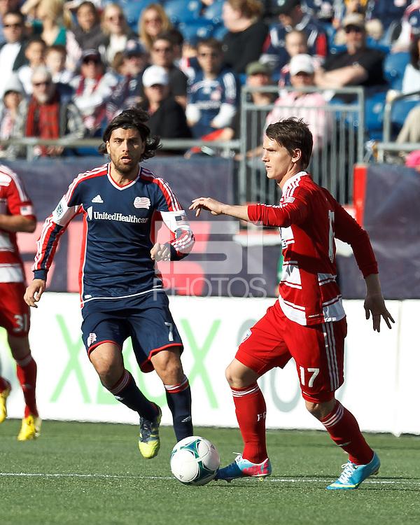 FC Dallas defender Zach Loyd (17) dribbles at midfield as New England Revolution forward Juan Toja (7) closes..  In a Major League Soccer (MLS) match, FC Dallas (red) defeated the New England Revolution (blue), 1-0, at Gillette Stadium on March 30, 2013.