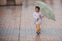 A Child Running With An Umbrella In Chongqing, China.  © LAN