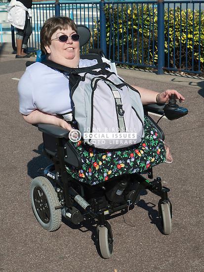 Wheelchair user going along a pavement