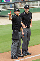 Home plate umpire Derek Gonzales signals that there is one more warm-up pitch as base umpire Tyler Ferguson looks on between innings of the South Atlantic League game between the West Virginia Power and the Kannapolis Intimidators at CMC-Northeast Stadium on April 30, 2014 in Kannapolis, North Carolina.  The Intimidators defeated the Power 2-1 in game one of a double-header.  (Brian Westerholt/Four Seam Images)