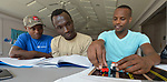 Martin Mayiani (right) teaches a class on driving at a Presbyterian church in Harrisonburg, Virginia. Mayiani is a former refugee who came to the U.S. four years ago. He volunteers to teach these newly arrived Congolese refugees how to pass the state's driving test, which isn't available in Swahili. They use toy cars to understand the nuances of how to drive in the U.S. <br /> <br /> Mayiani and his students were resettled in the Harrisonburg area by Church World Service.<br /> <br /> Photo by Paul Jeffrey for Church World Service.