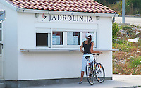 The white kiosk where you buy ferry boat tickets on the Korcula island. A woman with bicycle standing outside. Korcula Island. Korcula Island. Dalmatian Coast, Croatia, Europe.