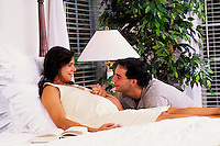 Caring husband and wife enjoying her pregnancy together at home