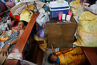 A religious statue is placed between a woman and a child resting in a church where hundreds of survivors of Typhoon Haiyan found shelter in Tacloban November 21, 2013. As millions of dollars pour in for more than four million left homeless by a typhoon in the central Philippines, authorities are grappling with a familiar problem - how to stop fraudulent claims and prevent greedy politicians taking advantage. Typhoon Haiyan smashed through the country on November 8, laying waste to just about everything in its path, and killing more than 4,000 people.