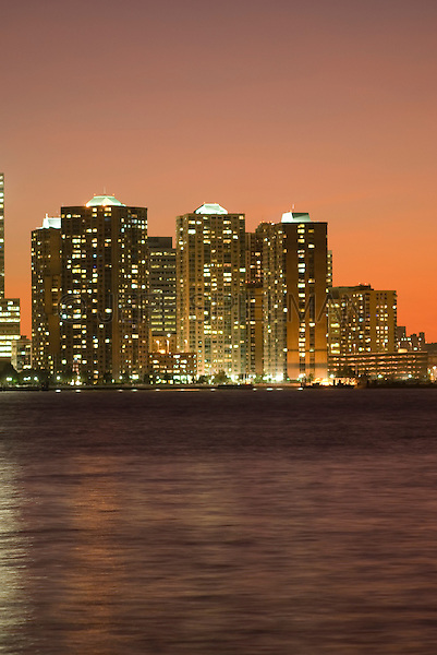 Modern Residental Apartment Buildings Illuminated at Dusk, Hudson River in the foreground, Jersey City, New Jersey, USA