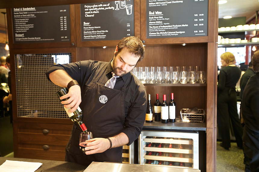 10/17/10 3:21:12 PM - Barista Supervisor Michael Rotman-Koenen pours a glass of wine at the wine bar in the newly remodeled Starbucks in Seattle. Starbucks is now offering wine, beer and dinner fare at their stores.