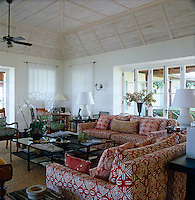 Red and white African batik fabric covers the comfortable sofas in the airy living room that opens onto shady terraces