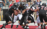 Lindenwood-Belleville QB Kerry Gibson (16, center) hands off to RB Antuan Davis (4, left) as Lindenwood linemen Zach Mitchell (51) and Nathanial Boggs (70) block an Avila player in the first half during the first football game in Lindenwood-Belleville history.