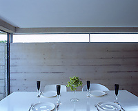Detail of the white dining table laid with white crockery and black glassware