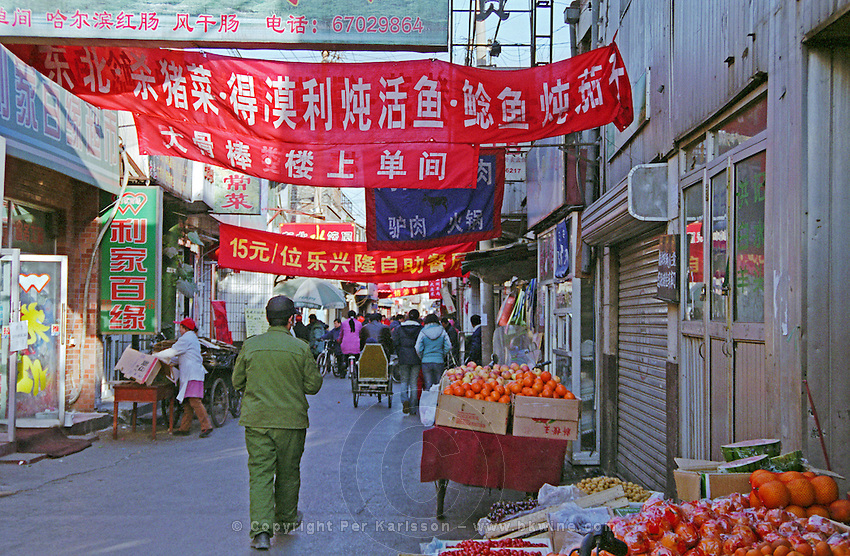 A hutong in Beijing - a market street, with red banners and lots of fruit.