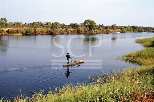 Zambia, Africa. A man standing in a dugout canoe with a bicycle on the river by Lake Chaya, going to Kabinga.
