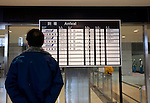 A man looks at the arrivals board while staff due to perform radiation checks await the arrival of a flight at Sendai airport in Natori, Miyagi Prefecture, Japan on 14 April, 2011. .Photographer: Robert Gilhooly