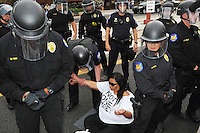 Phoenix, Arizona. April 25, 2012 - Phoenix Police officers arrest Danielle Nieto, one of the six protesters who blocked Central Avenue. About 500 people protested the controversial law on the same day U.S. Supreme Court justices heard legal arguments on the Arizona vs. United States case. At the end of the march, six activists blocked Central Avenue by sitting in the middle of the street. They all were arrested by the Phoenix Police Department and taken to the Fourth Avenue County Jail. Photo by Eduardo Barraza © 2012