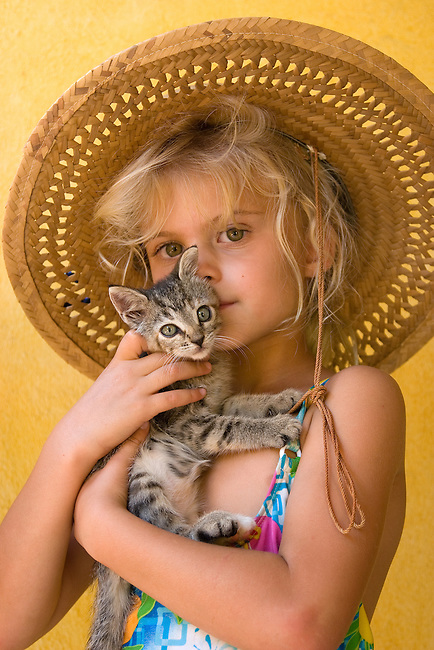 Mexico. Young girl embraces her kitten. MR