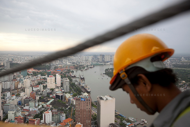 Construction workers work on The Financial Tower, a 68-story skyscraper, located in District 1 in Ho Chi Minh City, Vietnam. The building, owned by the Vietnamese company Bitexco Group, is designed in the shape of a lotus flower - a Vietnamese cultural symbol. As of 2007, the building was ranked 17th in the world among the tallest.