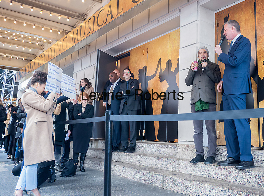 "New York Mayor Bill de Blasio, right, reads from Spanish cue cards as he addresses theater lovers with Lin-Manuel Miranda, left, in front of the Richard Rodgers Theatre in Times Square in New York on Wednesday, April 6, 2016 prior to the #Ham4Ham lottery for seats for the Broadway blockbuster ""Hamilton"". The $10 live lottery takes place in front of the theater for the Wednesday matinee performance while for the rest of the week's performances the lottery is online. (© Richard B. Levine)"