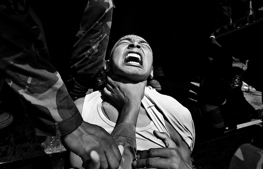 A Tibetan activist is choked by a Nepali policeman during a protest outside the Chinese Consulate against Chinese human rights violations, Kathmandu, Nepal, Saturday, August 9, 2008. Several hundred protesters were arrested and taken to a detention center after some broke through the line of police and spray-painted the first three letters of the word 'Tibet' on the outer wall of the Chinese Consulate.
