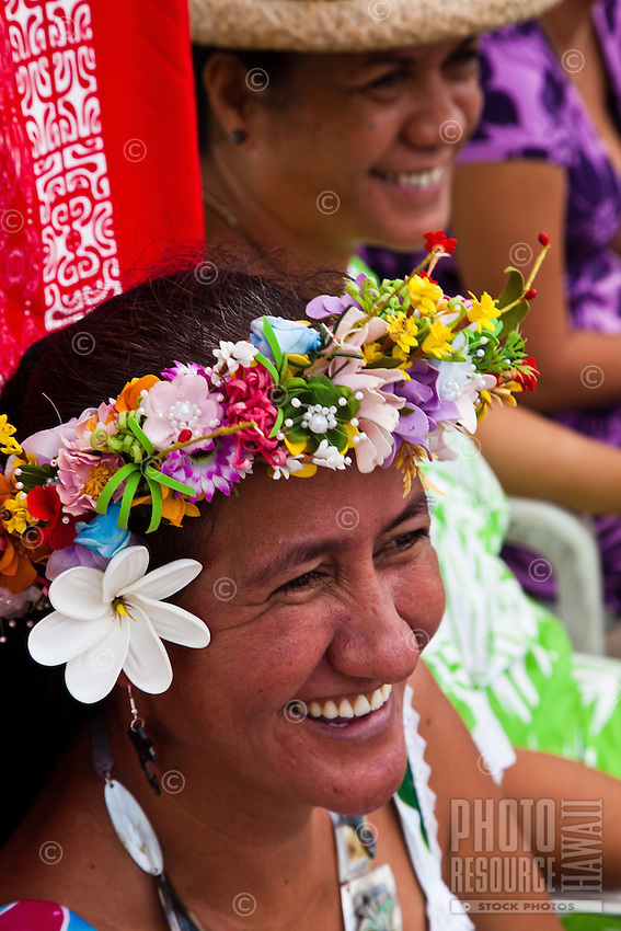 Tahitian women smiling and wearing head lei and flowers