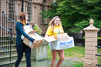 Haylee Torres,'20, and Rebkah Rhein,'20, haul boxes to the trash bins at the Redwood Library in Newport as they take part in Salve's Exploration Day of Service
