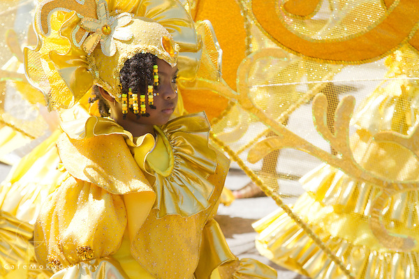 """Junior carnival street parade - from Rosalind Gabriels' band """"50 Years Gold"""" Heralds of Gold section. Young girl in yellow with braids - side view"""