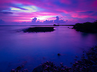 At sunset, a canopy of vivid pink and purple clouds drift over Kiholo Bay, Big Island.