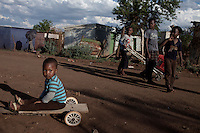 KHUTSONG, SOUTH AFRICA - OCTOBER 16: Children play on October 16, 2012, in Khutsong, South Africa. Khutsong, a black township. is located about 56 miles west of Johannesburg, and surrounded by gold mines. Because of recent strikes many mineworkers has been fired which is making the poverty worse here. (Photo by Per-Anders Pettersson)