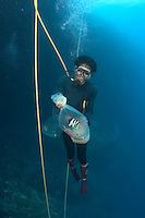 This tropical reef fish collector illegally uses cyanide to capture these uncommon deep water species.  Indonesia.