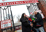 TORRINGTON CT. 23 December 2017-122217SV01-Crystal Mahoney with Rylan Jacques, 3, and Hunter Jacques, 3, and Robert Jacques all of Torrington get their picture taken in front of the Christmas Village in Torrington Saturday. They were waiting in line to see Santa. <br /> Steven Valenti Republican-American