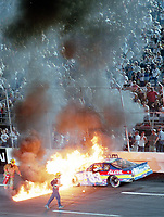 Firefighters work to extinguish the flames from Tony Raines' race car after a crash in a NASCAR Busch Series race in Richmond, VA on Friday, September 8, 2000.  Raines was not injured in the accident.  (Photo by Brian Cleary)
