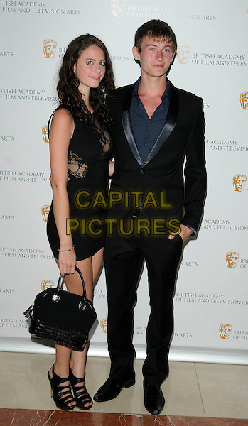 KAYA SCODELARIO & ELLIOTT TITTENSOR.British Academy Television Craft Awards at the Hilton, Park Lane, London, England. .May 23rd 2010 .BAFTA full length dress mini black lace sleeveless sheer see thru through open toe shoes sandals suit blue grey gray shirt couple.CAP/CAN.©Can Nguyen/Capital Pictures.