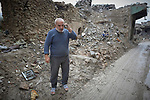 A man talks on his mobile phone amid the rubble of the Old City of Mosul, Iraq, which was devastated during the 2017 Battle of Mosul, which led to the defeat of the Islamic State group, also known as ISIS.