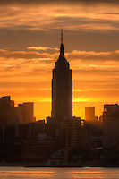 The rising sun shines from behind the Empire State Building just after sunrise