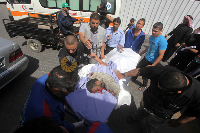 Palestinian medical workers transfer a martyr into al-Shifa hospital following an Israeli raid on Gaza City, on April 30, 2013. An Israeli air strike on Gaza City killed one person and wounded another, Gaza's Hamas-run health ministry said. Photo by Ashraf Amra
