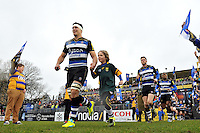 Francois Louw, mascot in hand, leads the Bath Rugby team out onto the field. Aviva Premiership match, between Bath Rugby and Wasps on February 20, 2016 at the Recreation Ground in Bath, England. Photo by: Patrick Khachfe / Onside Images