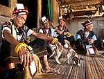 Men in ceremonial dress relaxing on the porch of a traditional home, Luba Village, near Bajawa, Flores, East Nusa Tenggara, Indonesia