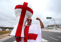 An England fan with a huge World Cup trophy with the St George's flag painted on outside Arena Corinthians