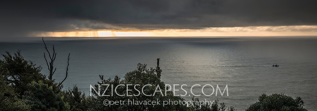 Fishing boat in Tasman Sea at sunset, West Coast, South Westland, New Zealand