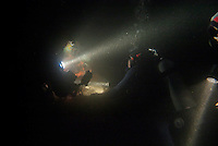 People scuba diving at night in the dark ocean.