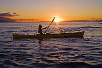 A female paddles a yellow kayak at sunset at Lahaina, Maui.