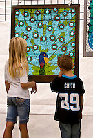 Visitors to Charlotte's Festival in the Park looks over artwork available for purchase.  For more than four decades, Charlotte's annual Festival in the Park has brought music, art and fun to Charlotteans and visitors. The festival has been chosen as one of Sunshine Artists Magazine's 200 Best Festivals.