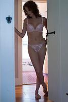 Woman wearing lingerie standing in hallway