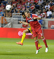 Chicago midfielder Logan Pause (12) heads the ball in front of Columbus midfielder Justin Meram.  The Chicago Fire defeated the Columbus Crew 2-1 at Toyota Park in Bridgeview, IL on June 23, 2012.
