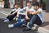 Group of teenaged boys sitting on a street corner chatting,