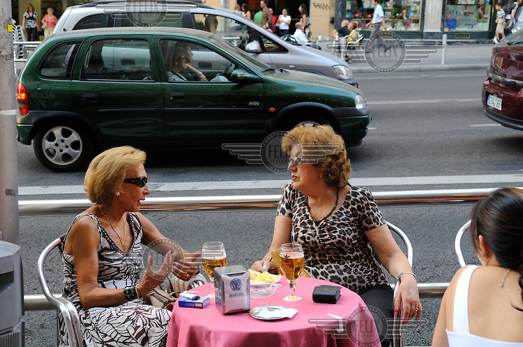 Two women talking in a pavement cafe by a main road in Madrid city centre.