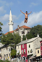 Un ragazzo si tuffa dal ponte di Mostar. The young muslims in Mostar resume traditional diving from bridge. The 16th-Century bridge was blown up during the bitter fighting in the Bosnian war between the city's Muslims and Croats in 1993. Its reopening after 11 yers, is being seen as symbolic of the healing of divisions between Muslims and Croats.