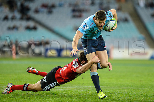 23.05.2015.  Sydney, Australia. Super Rugby. NSW Waratahs versus the Crusaders. Waratahs Rob Horne is wrapped up by a diving tackle while on the break. The Waratahs won 32-22.